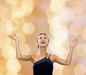 people, happiness, holidays and glamour concept - smiling woman raising hands and looking up over beige lights background