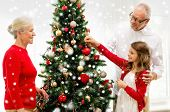 family, holidays, generation and people concept - smiling family decorating christmas tree at home