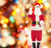 christmas, holidays, gesture and people concept - man in costume of santa claus pointing finger up over red lights background