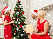 christmas, holidays, happiness and people concept - smiling family in santa helper hats with gift box at home