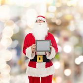 christmas, advertisement, technology, and people concept - man in costume of santa claus with tablet pc computer over lights background