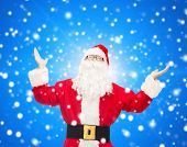 christmas, holidays and people concept - man in costume of santa claus with raised hands over blue snowy background