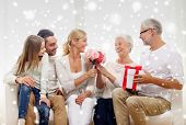 family, happiness, generation, holidays and people concept - happy family with bunch of flowers and gift box sitting on couch at home