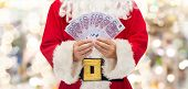 christmas, holidays, winning, currency and people concept - close up of santa claus with euro money over lights background