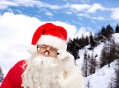 christmas, holidays and people concept - close up of santa claus in glasses winking over snowy mountains