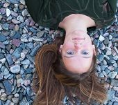 Young beautiful girl lying on the river pebbles, top view closeup portrait.