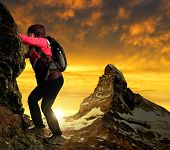 Girl on rock, in the background mount Matterhorn at sunset Swiss Alps, Europe