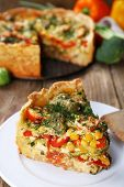 Piece of Vegetable pie with broccoli, peas, tomatoes and cheese on plate, on wooden background