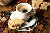 Cup of coffee and tasty cookie on wooden background