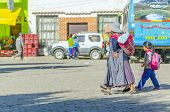 COPACABANA, BOLIVIA, MAY 6, 2014:  Local woman in traditional costume  walks down the street with a daughter and wears a baby on her back