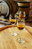 Glasses of wine in cellar with old barrels