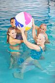 Happy family with senior couple playing with water ball in swimming pool