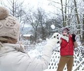 Man and woman doing a snowball fight in winter