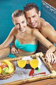 Happy couple having breakfast in swimming pool