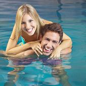Happy couple having fun in a swimming pool in a hotel in summer