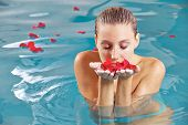Attractive young woman in water with petals of roses in her hands