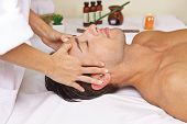 Relaxed man in health resort spa getting head massage
