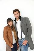Trendy couple of lovers standing on white background