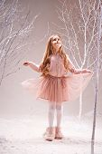 Cute little girl in pink dress walking in magic forest among bare trees