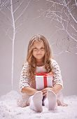 Adorable little girl with giftbox looking at camera