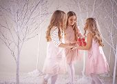 Cute playful girls dancing in fairy winter forest