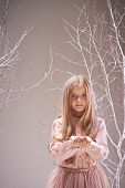 Adorable child with heap of snowflakes on her palms looking at camera
