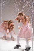 Playful girls in smart dresses playing snowballs in winter forest