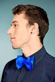 Close-up portrait of an imposing young man in formal shirt and bow-tie. Men's beauty, fashion.