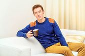 Portrait of a handsome young man at home, drinking tea or coffee and smiling at camera.