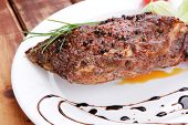 meat on wooden plate : roast shoulder on wood with tomatoes chives and green lettuce on white plate