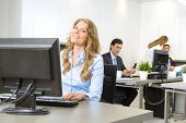 Happy businesswoman at her desk, with people working at the background