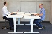two men  coworking in correct sitting posture on pneumatic leaning seats  with laptops  at electric height adjustable desks in office