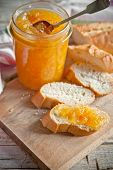 orange jam in a glass jar and bread on background wooden plank