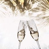 Toasting with champagne against fireworks