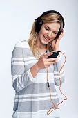 young girl with mp3 player listening to music on headphones