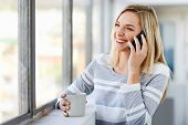 young woman chatting on phone while standing at the window and drinking coffee