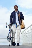 Happy smiling walking bike in the city african black man