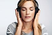 Portrait of young woman listening to music on dj headphones