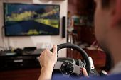 Постер, плакат: Man playing racing game with steering wheel simulator
