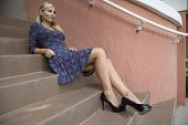 Female Model Sitting On Stairway Wearing Dress And Heels