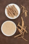 Ginseng ashwagandha herb root and powder over handmade lokta paper background.