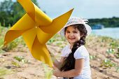Cheerful dark-haired girl playing with windmill