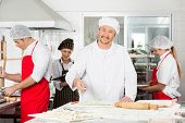 Portrait of smiling male chef sprinkling flour on ravioli pasta with colleagues working in background at commercial kitchen
