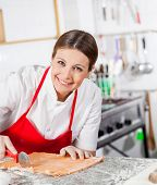 Portrait of happy female chef cutting ravioli pasta at counter in commercial kitchen