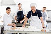 Portrait of confident chefs preparing pasta at commercial kitchen