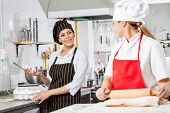 Happy female chefs conversing while preparing pasta in commercial kitchen