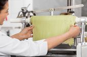 Cropped image of chef adjusting ravioli pasta sheet in machinery at commercial kitchen