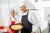 Portrait of confident male and female chefs with pizza pan at commercial kitchen