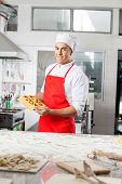 Portrait of smiling male chef holding tray with stuffed ravioli pasta sheet in commercial kitchen