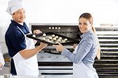 Portrait of happy female chef giving baking sheet to male colleague by oven in commercial kitchen
